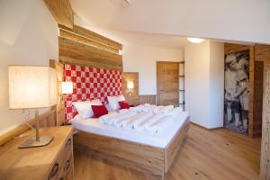 Ferienwohnung in Reit im Winkl: Alpenländischer Luxus im Stadl-Stil mit Massivholzbett und begehbarem Kleiderschrank.