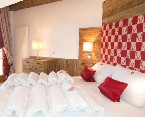 Schlafzimmer Ferienwohnung Kaiserwinkl Suite mit Altholz und Blick auf Balkon und Kaisergebirge in Reit im Winkl