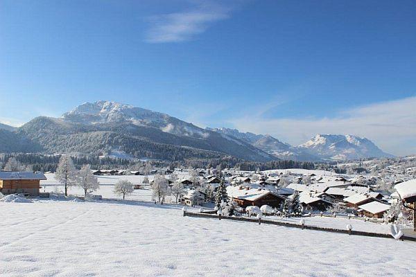 Ferienwohnungen Neumaier Reit im Winkl Blick vom verschneiten Garten auf Dorf und Berpanorama