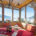 Ferienwohnung Kaiserwinkl Panorama, Sitzecke mit Panoramafenster und Blick auf Winterlandschaft, TV und Elektrokamin, Label Angebot