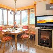 Ferienwohnung Kaiserwinkl Panorama, Sitzecke mit Panoramafenster, TV und Elektrokamin, Label Angebot
