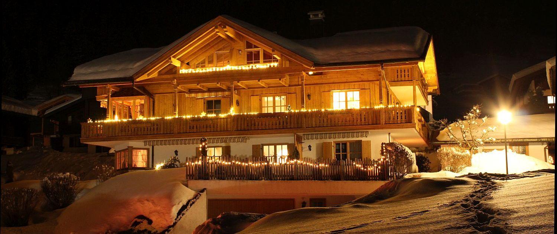Ferienhaus Neumaier in Reit im Winkl, tief verschneit und hell erleuchtet bei Nacht