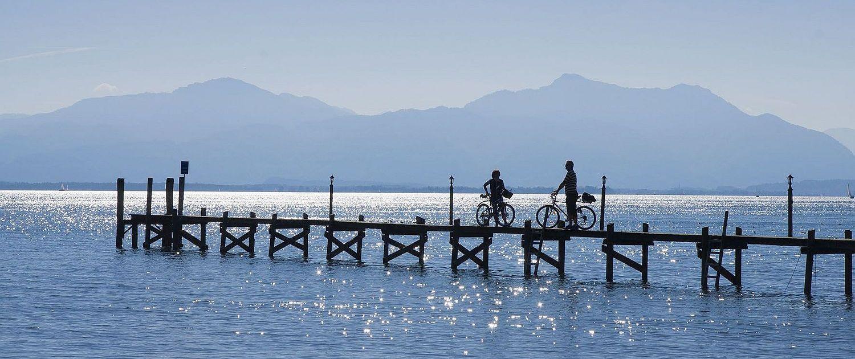 Chiemsee im Chiemgau / Oberbayern zwei Radfahrer stehen auf Steg
