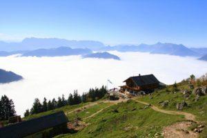 Blick auf Hochgern-Haus von Hochgern-Gipfel mit Nebel über Tal im Chiemgau Oberbayern