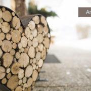 Herz aus Holzscheiten vor Haus von Ferienwohnungen Neumaier Reit im Winkl