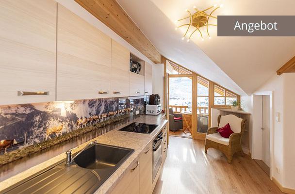 Ferienwohnung in Reit im Winkl, Blick auf moderne Küche und Balkon mit Bergblick; Beitragsbild für Angebot Ferienwohnungen Neumaier