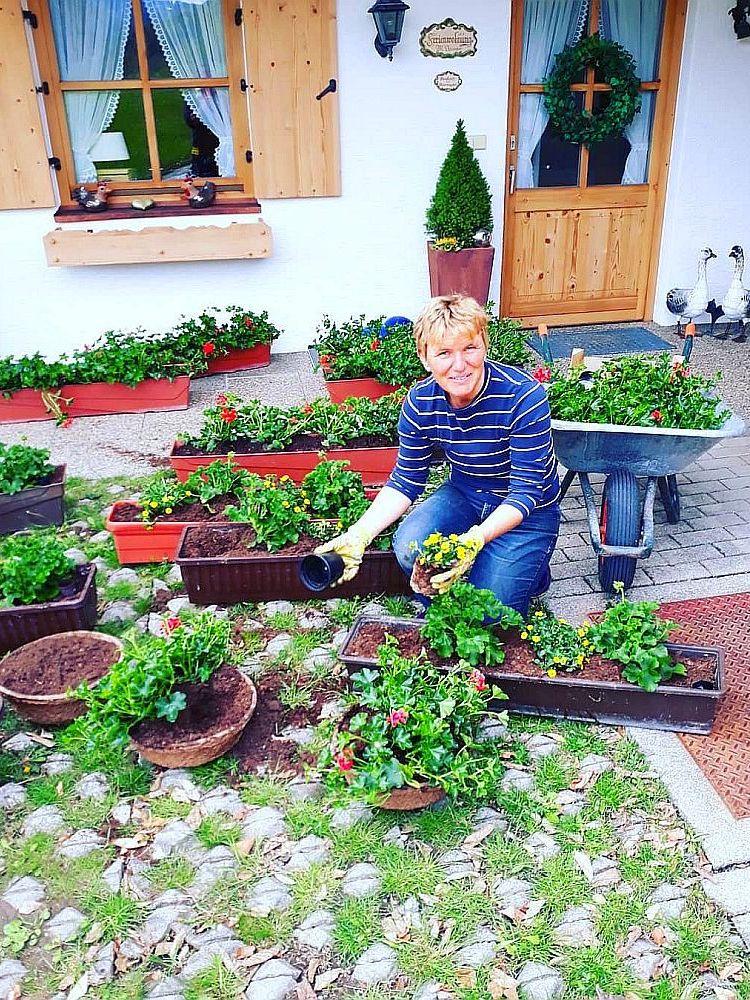 Christa Neumaier vor Ferienhaus in Reit im Winkl beim Gärtnern