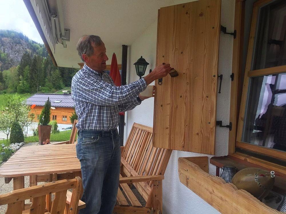 Michael Neumaier streicht Klappladen von Haus Ferienwohnungen Neumaier Reit im Winkl