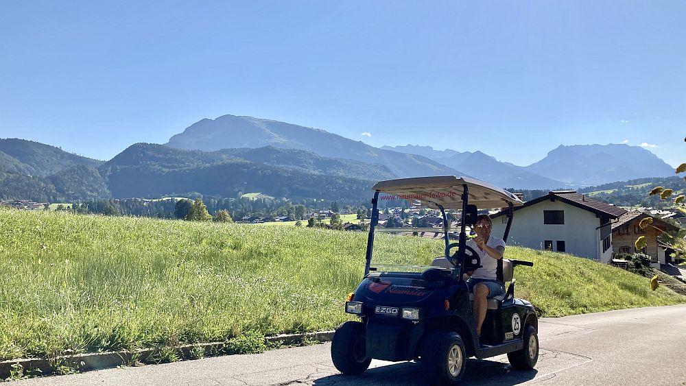 E-Golfcart von Ferienwohnungen Neumaier in Reit im Winkl, Christa Neumaier in Golfcart, Bergpanorama im Hintergrund